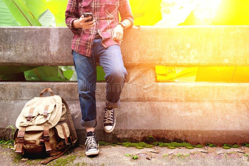 Portrait avant d'un voyageur de jeune homme il utilise le téléphone portable photo libre de droits