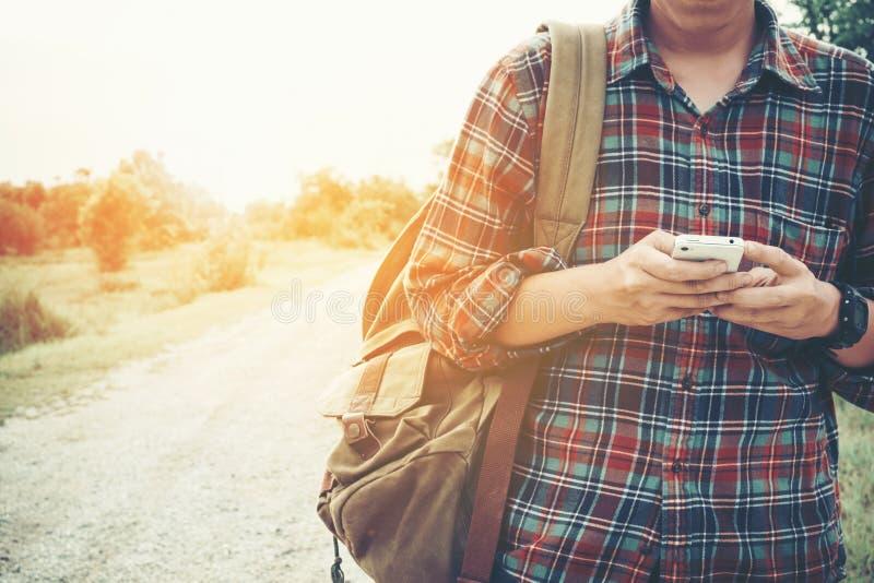 Portrait avant d'un voyageur de jeune homme il utilise le téléphone portable photos stock