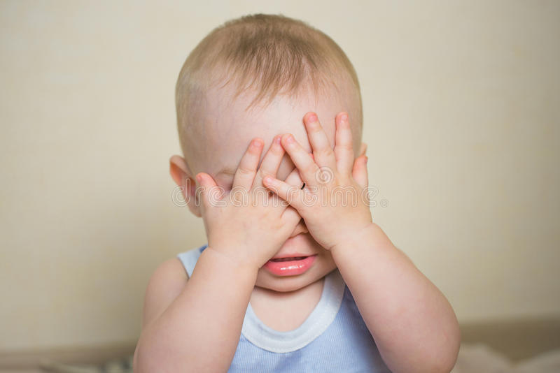 Portrait of baby boy closed his eyes with hands to be invisible or not willing to see, playing fun peek a boo.  stock image