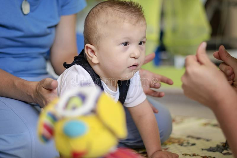 Portrait of a baby with cerebral palsy on physiotherapy in a children therapy center. Boy with disability has therapy by doing royalty free stock photography