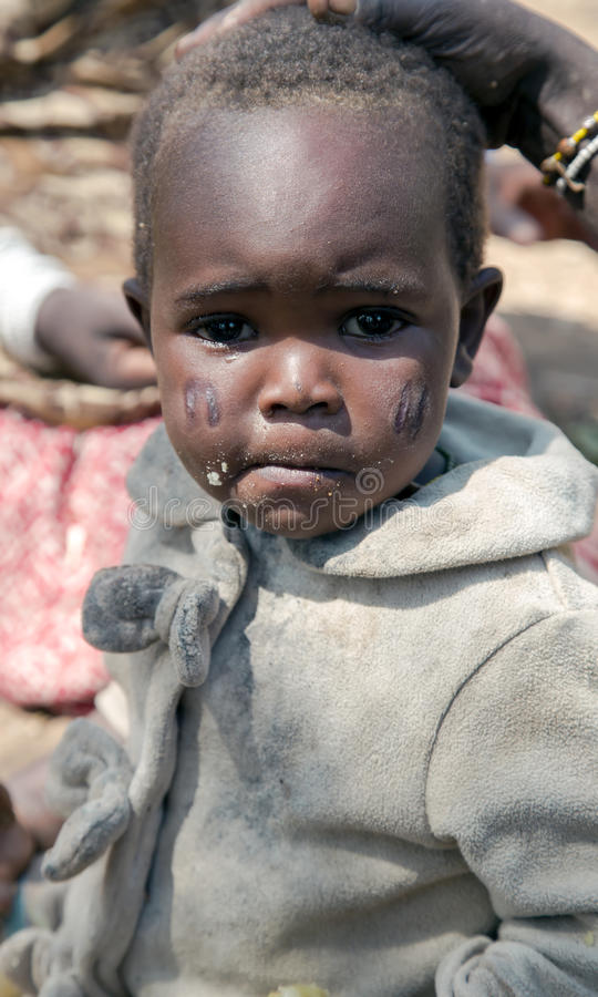 Portrait of a baby closeup of a Hadza tribe. AFRICA, TANZANIA, MAY, 10, 2016 - Portrait of a baby closeup of a Hadza tribe. Searing cheeks - a mandatory stock image