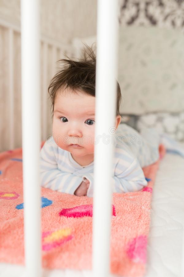Portrait of a baby in the crib. High angle portrait of a beautiful baby with a finger in his mouth, lying on the bed, his eyes. Wide open, woke up after sleep royalty free stock image