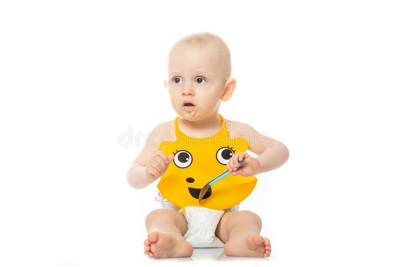 Portrait of a baby with a dirty face. isolated on white, cute happy caucasian baby boy in yellow bib, sitting with a spoon baby. Food in hands royalty free stock photography