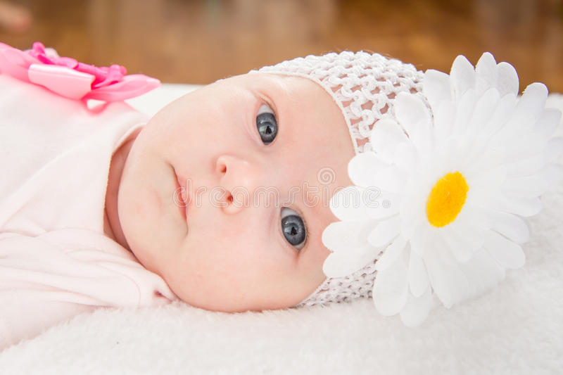 Portrait of a baby girl with a bandage on his head and a flower. A two-month baby girl Europeans on the back with a bandage on his head with a flower lying on a royalty free stock photos