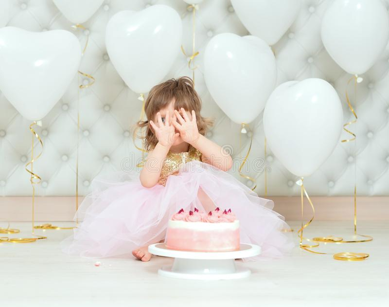 Portrait of baby girl with cake on her birthday. Baby girl with cake on her birthday posing at home royalty free stock photography