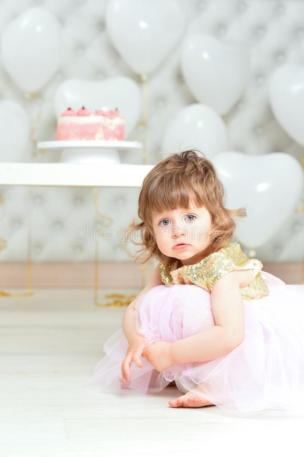 Portrait of baby girl with cake on her birthday. Baby girl with cake on her birthday posing at home royalty free stock photo