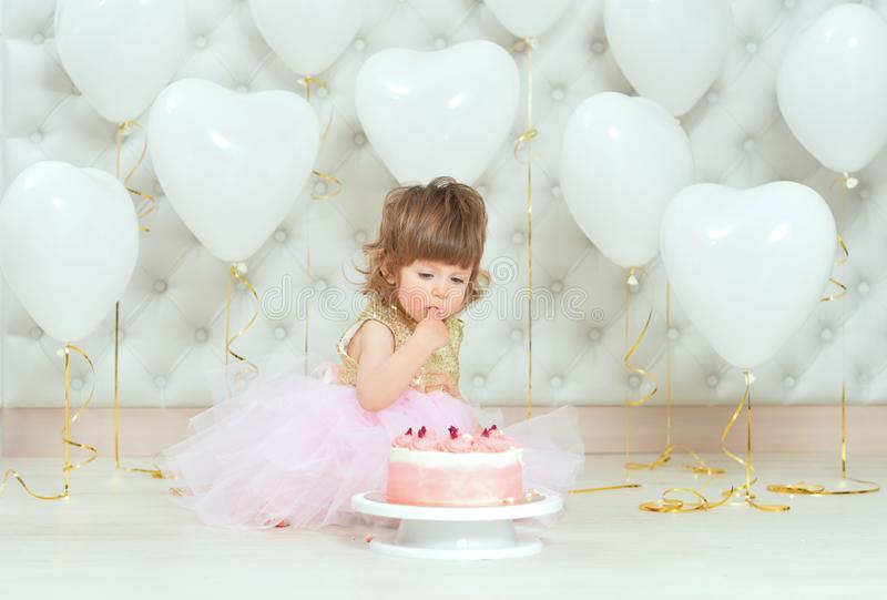 Portrait of baby girl with cake on her birthday. Baby girl with cake on her birthday posing at home royalty free stock images