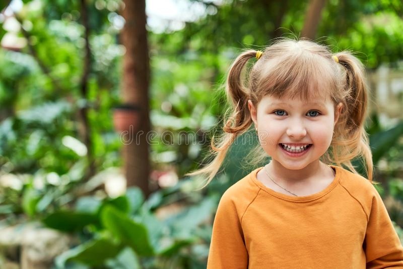 Portrait of a baby girl in the jungle. cheerful child in the zoo. Positive smiling baby girl with blonde hair with two tails royalty free stock photo