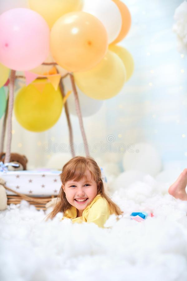 Portrait of a baby girl lying on a cloud next to a basket of balloon in the clouds, traveling and flying in dreams. Concept of freedom of creativity or royalty free stock image