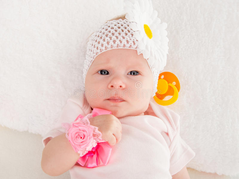 Portrait of a baby girl lying two-year. A two-month baby girl Europeans on the back with a bandage on his head with a flower lying on a soft bed stock images