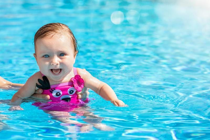 Portrait of a baby girl in a swimming pool stock photo