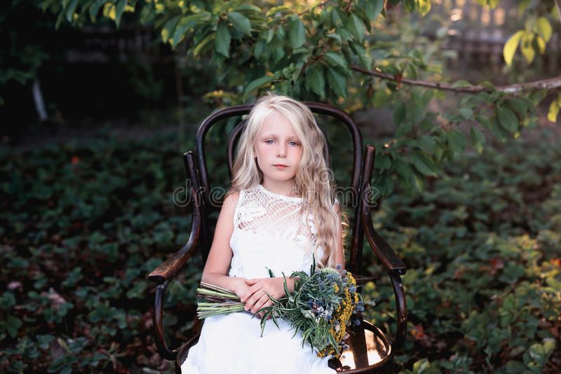 Portrait of a baby girl on vintage chair with a bright bouquet of flowers stock image