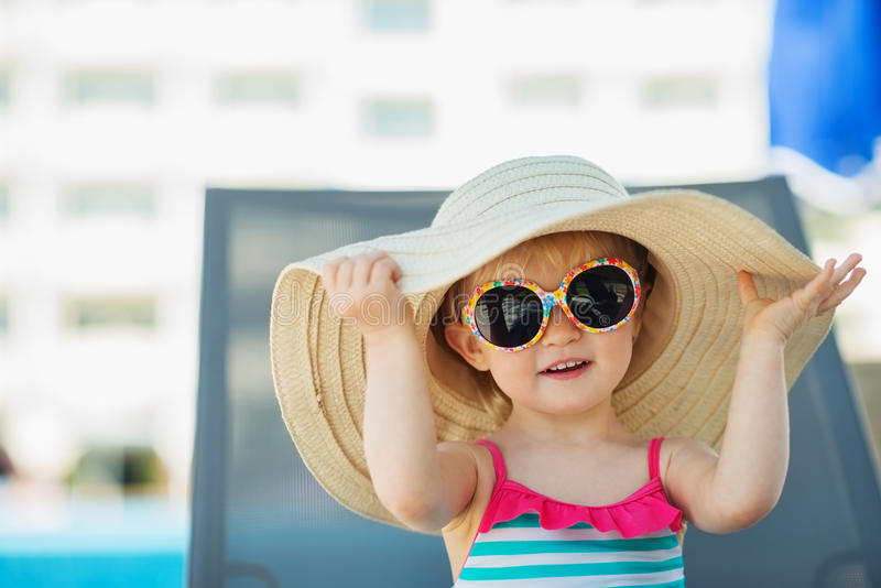 Portrait of baby in hat and glasses. Sitting on sun bed royalty free stock image