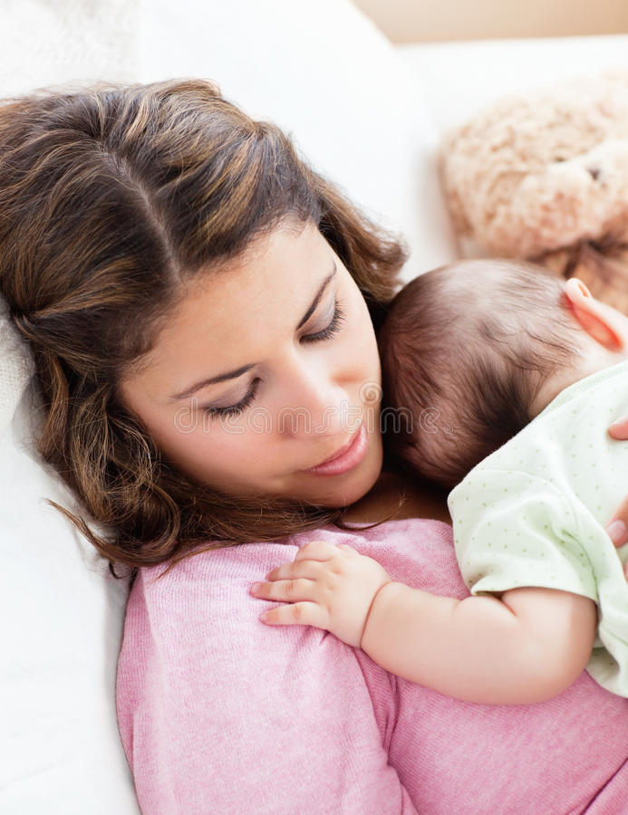 Portrait of a baby and his mother sleeping. Peacefully in the sofa at home royalty free stock image