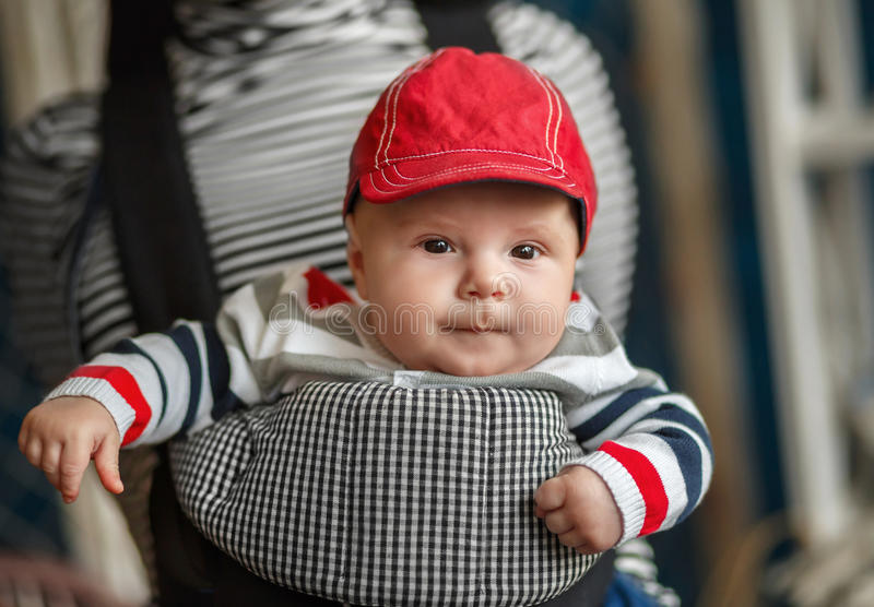 Portrait of a baby sitting in an ergonomic baby carrier stock images