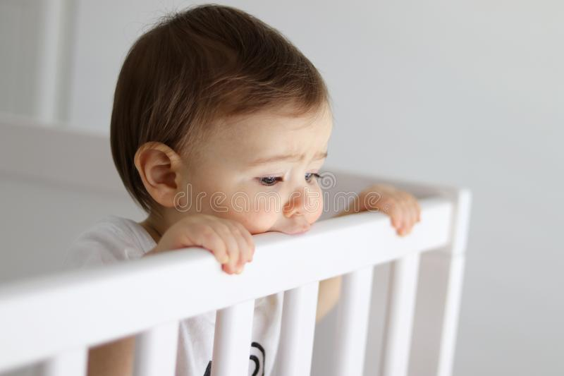 Portrait of baby staying in his baby cot looking sadly. Outside with frowned brows royalty free stock image