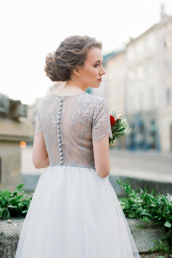 Portrait from the back of pretty young woman in amazing wedding dress holding flower bouquet while standing outdoors in. The stairs. Old city in the morning stock photos