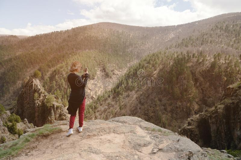 Portrait from the back of a traveling girl taking pictures of an epic landscape with rocks on her smartphone stock images