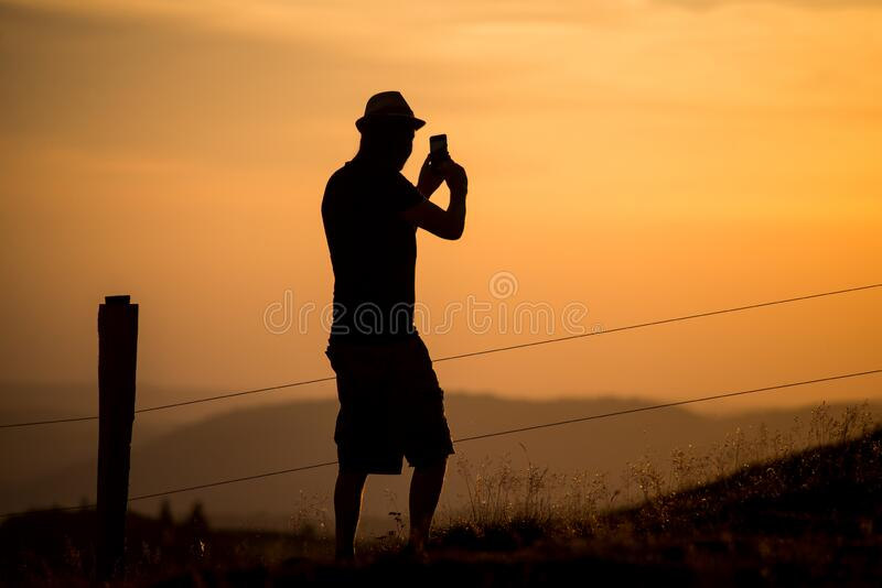 man silhouette standing at the top of the mountain taking a photography  with his smatphone in hands on royalty free stock photography