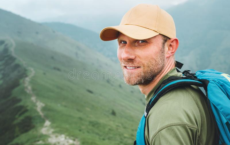Portrait of backpacker man in baseball cap walking by the foggy cloudy weather mountain range path with backpack. Active sports royalty free stock photos