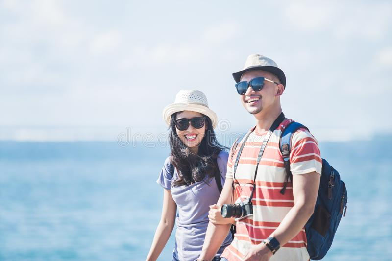 Backpackers couple wearing summer hat and sunglasses walking on royalty free stock photography