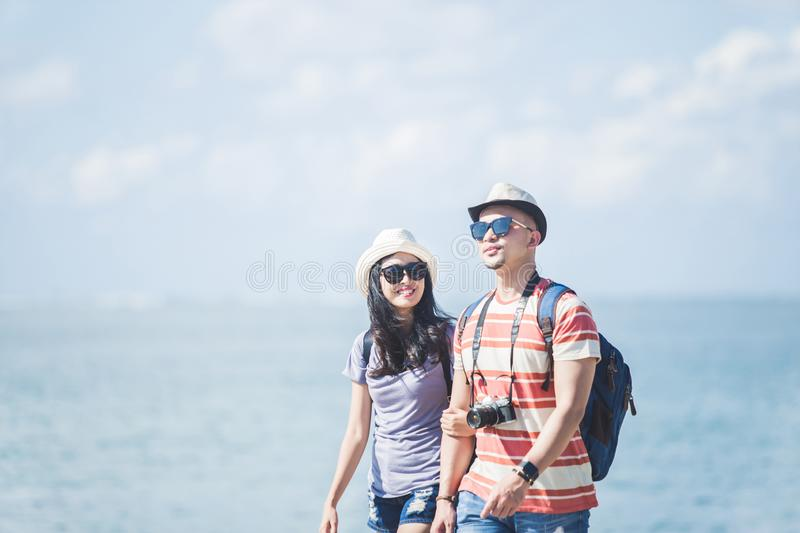 Backpackers couple wearing summer hat and sunglasses walking on. Portrait of backpackers couple wearing summer hat and sunglasses walking on the seashore during royalty free stock photo