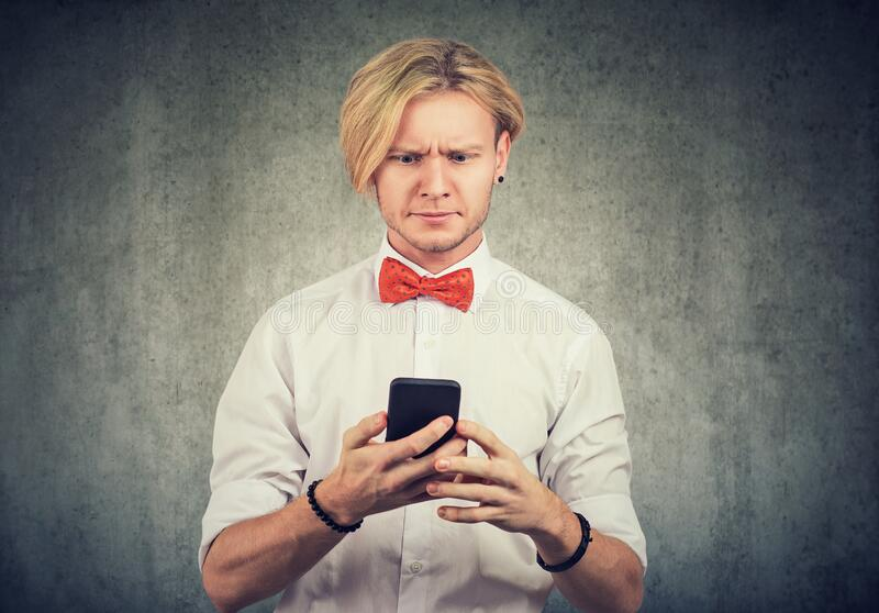 Portrait of a baffled looking man reading bad news on his smartphone stock image