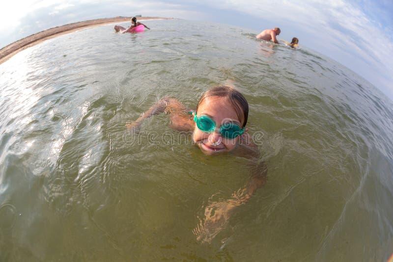 Portrait, bains heureux de petite fille en mer avec des verres image stock