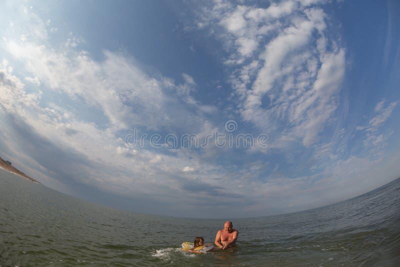 Portrait, bains heureux de petite fille en mer sur un cercle gonflable photographie stock