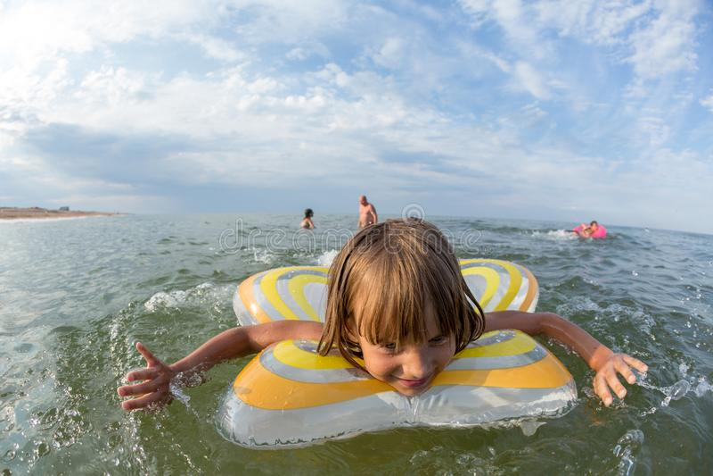 Portrait, bains heureux de petite fille en mer sur un cercle gonflable images stock