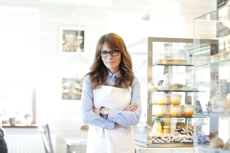 Portrait of bakery shop owner. Smiling, beautiful mature woman. Small business bakery shop owner standing in her store stock photos