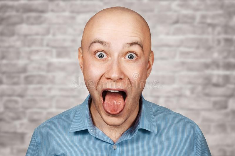Portrait bald adult guy opened his mouth and shows tongue at the doctor`s reception on brick wall white background.  royalty free stock image