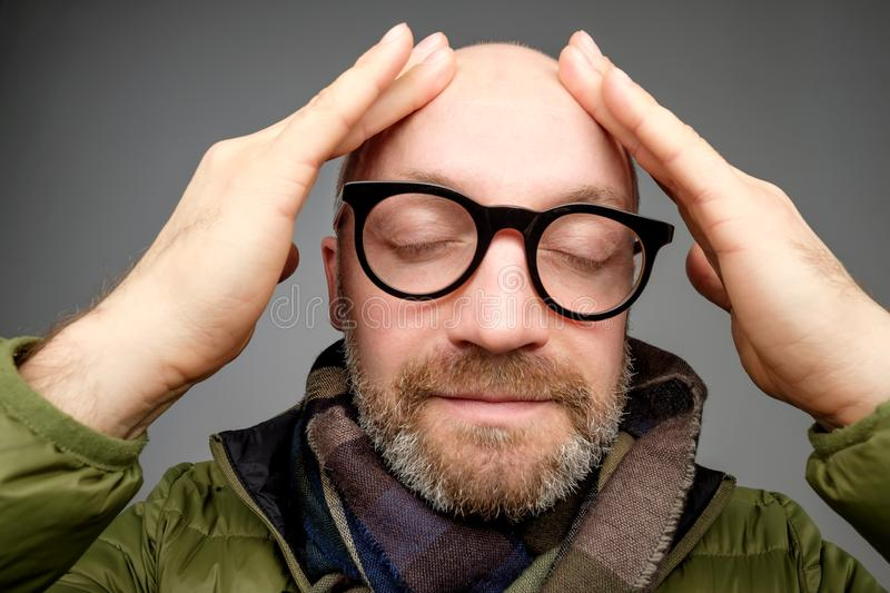 Portrait of bald adult man with beard toching his head with fingers. He is calm and content stock photography