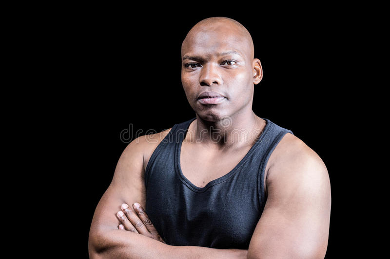 Portrait of bald bodybuilder with arms crossed. Against black background royalty free stock photo