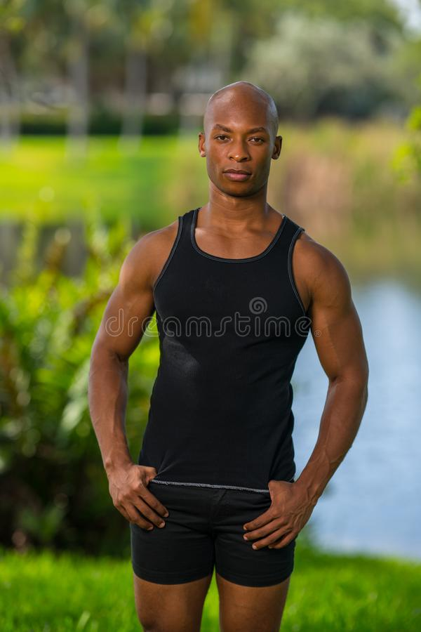 Portrait of a bald fitness model posing in a tank top t-shirt royalty free stock image
