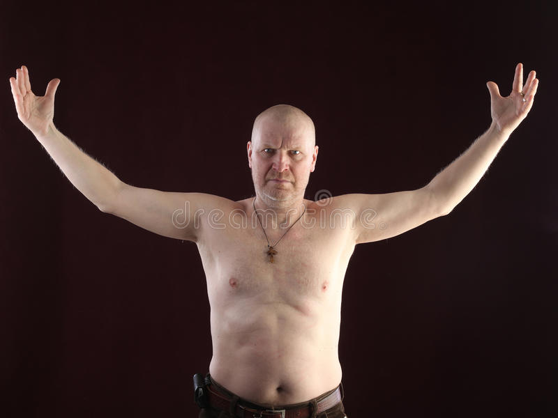 Portrait of a bald man. Close-up portrait on a belt adult bald man with a naked torso and a cross on his chest on a dark background studio royalty free stock photo