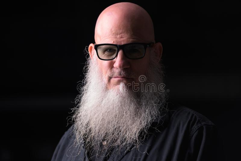 Portrait Of Bald Man With Gray Beard Outdoors At Night stock image
