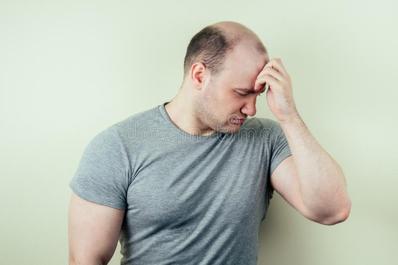 A portrait of a bald man is sad against a gray background. problem of male pattern baldness. sadness, vexation and anger royalty free stock photography