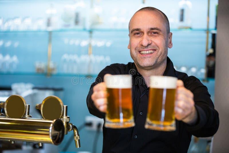 Portrait of bar tender offering beer. Portrait of happy bar tender offering beer at bar stock images