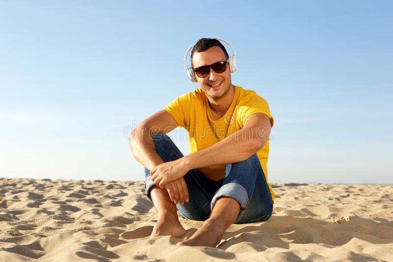 Barefoot man sitting in sand at the beach listening to music with headphones. Portrait of barefoot man sitting in sand at the beach listening to music with royalty free stock images