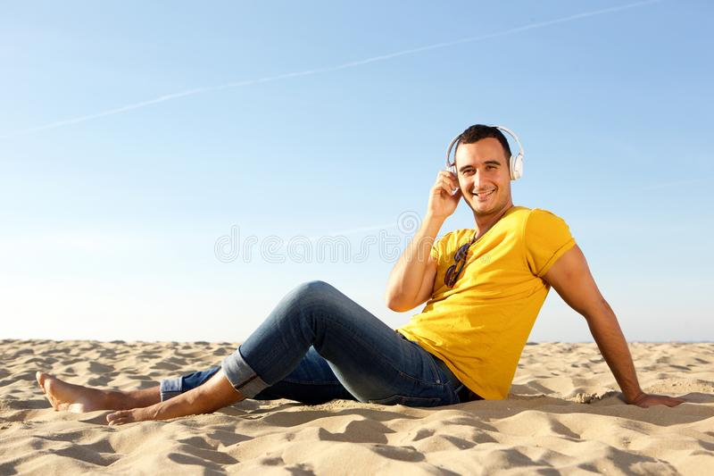Barefoot smiling man sitting in sand at the beach listening to music with headphones. Portrait of barefoot smiling man sitting in sand at the beach listening to royalty free stock photo