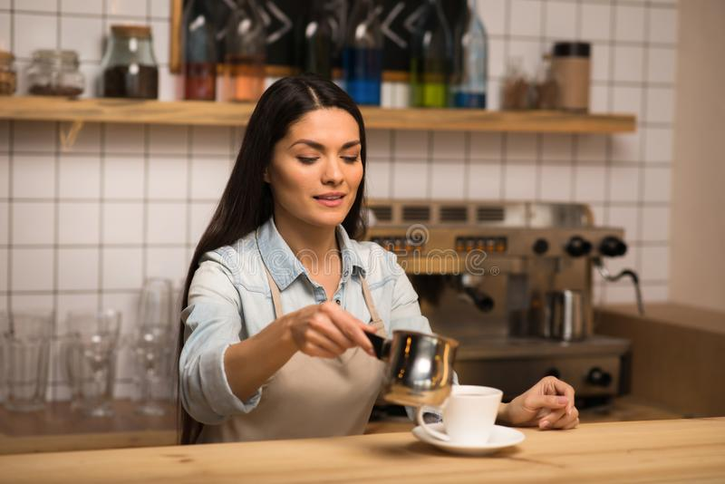 Barista pouring milk into coffee. Portrait of barista pouring milk into coffee stock images