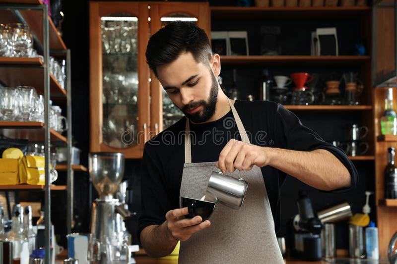 Portrait of barista pouring milk into cup of coffee against bar shelves royalty free stock images
