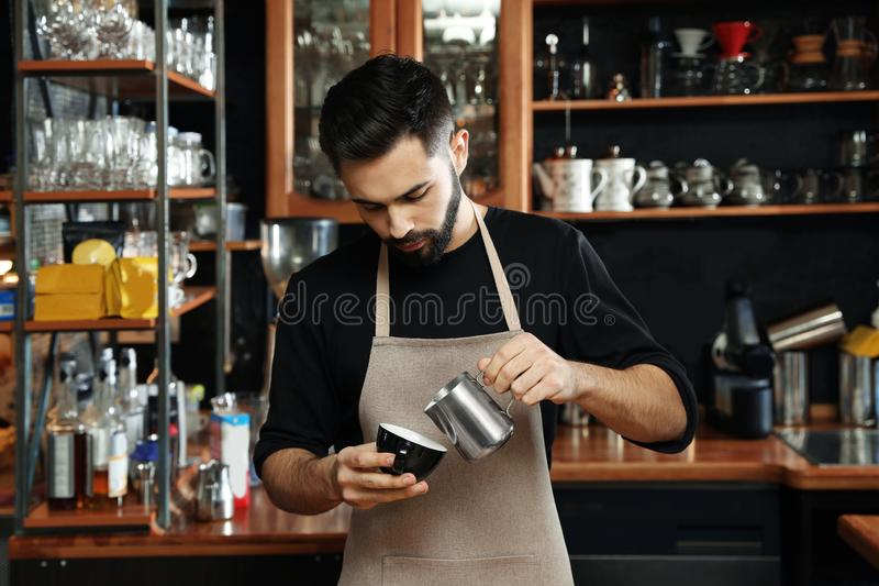 Portrait of barista pouring milk into cup of coffee against bar shelves royalty free stock photo