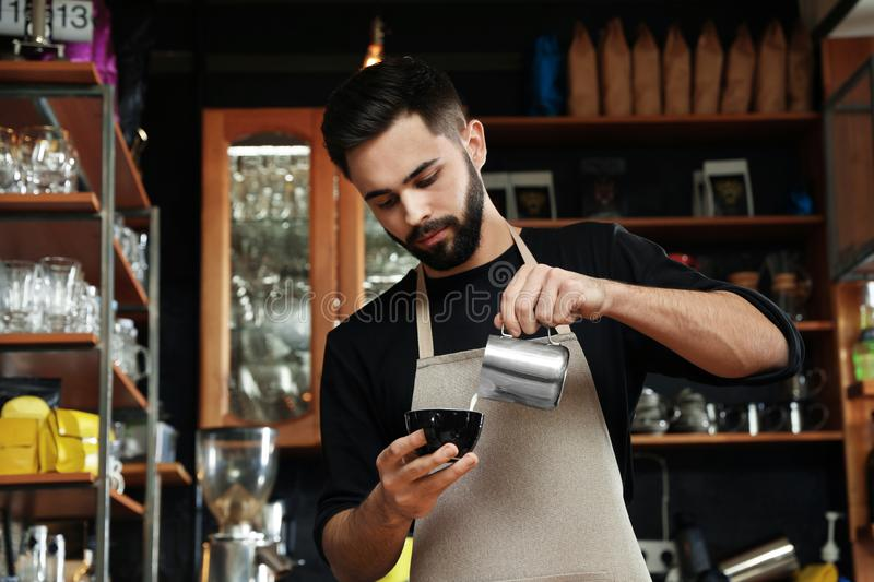 Portrait of barista pouring milk into cup of coffee against bar shelves stock image