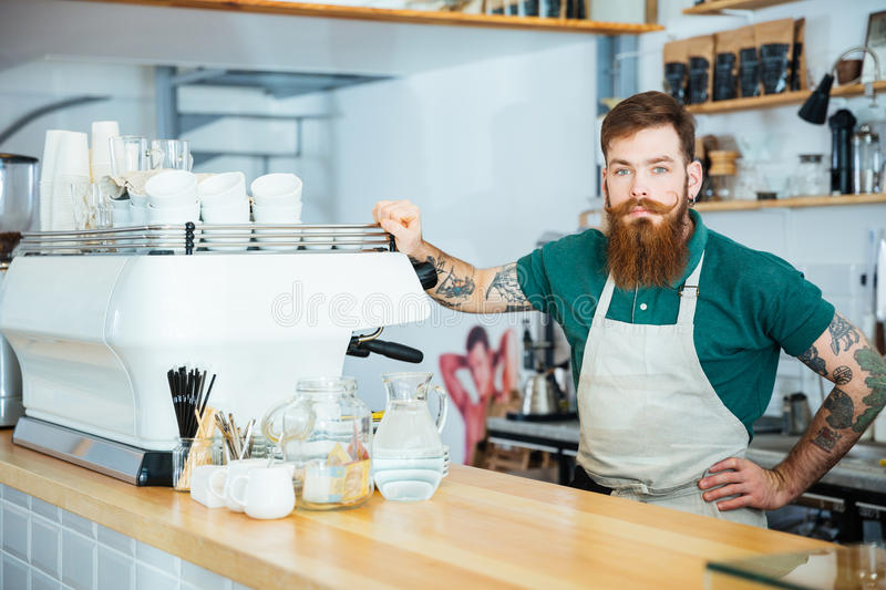 Portrait of barista standing near coffe machine in coffee shop. Portrait of handsome barista with beard and tattoo on hands standing near coffe machine in coffee royalty free stock photography