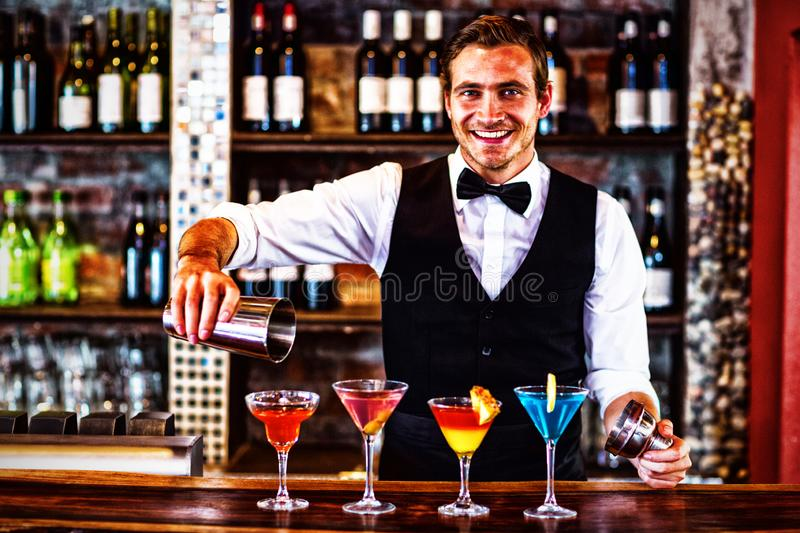 Portrait of bartender pouring a orange martini drink in the glass. At bar royalty free stock image