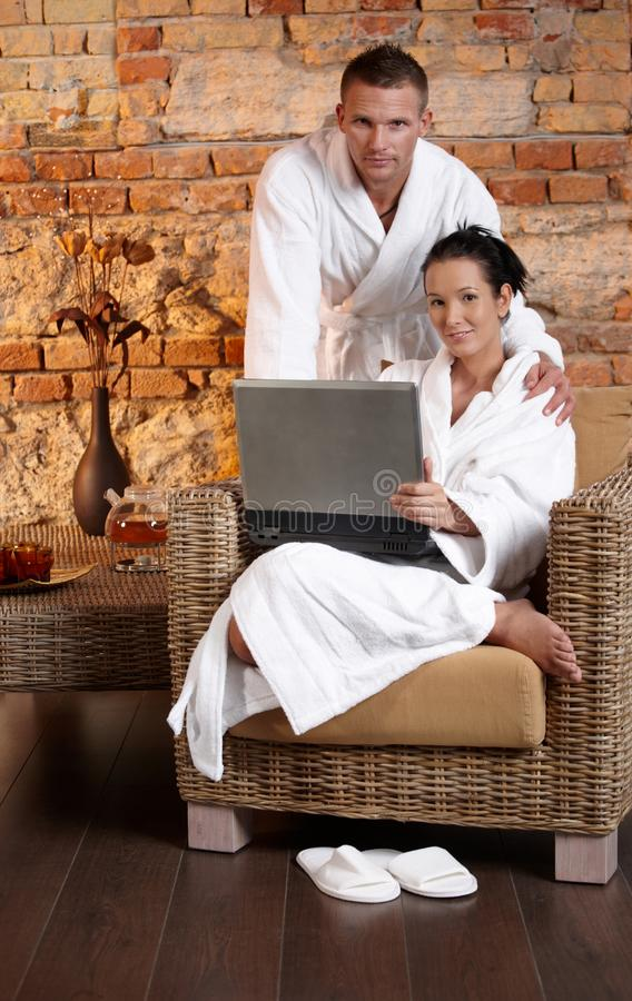 Portrait Of Bathrobe Couple With Laptop Stock Images