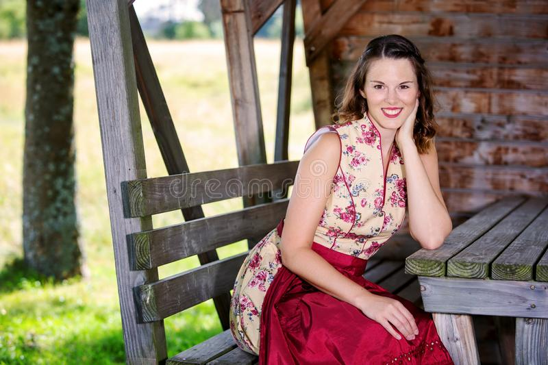 Bavarian woman in dirndl sitting in a hut stock photography