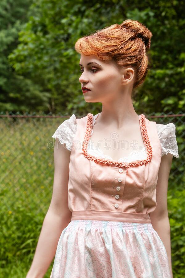 Portrait of a Bavarian young woman. Traditional costume worn by a young model with reddish plug-in hairstyle stock photos